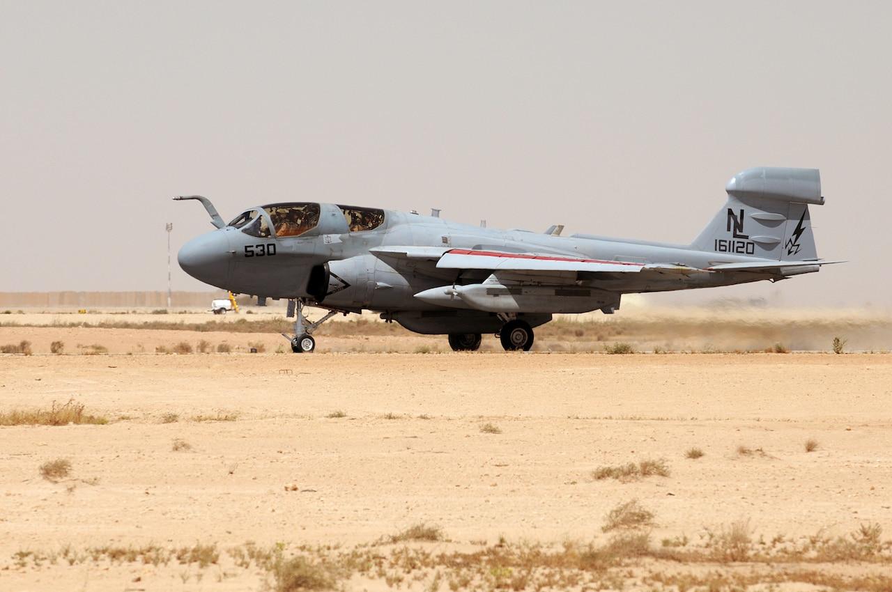 A military aircraft moves down a runway.
