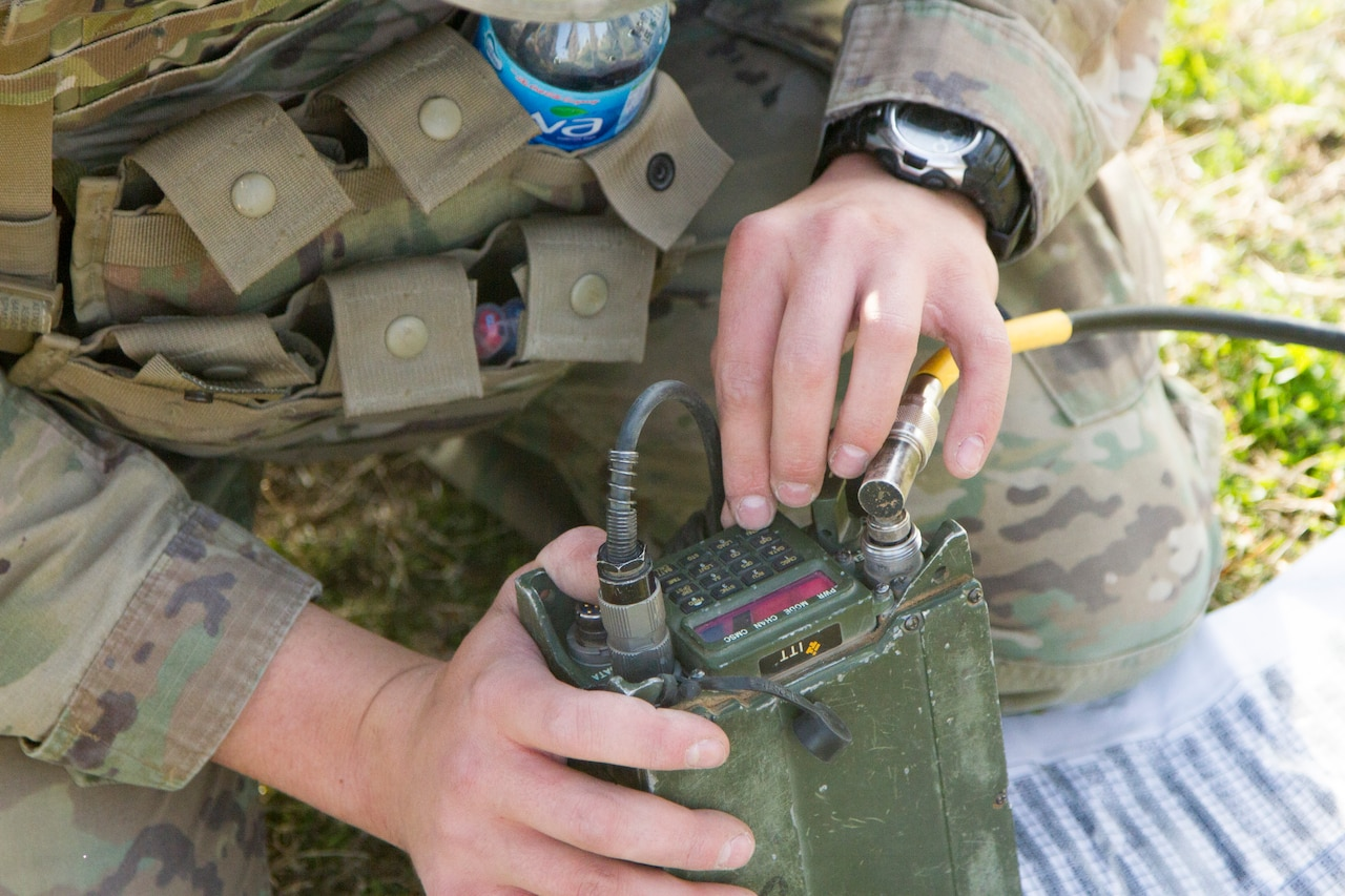 Two hands hold a military radio.