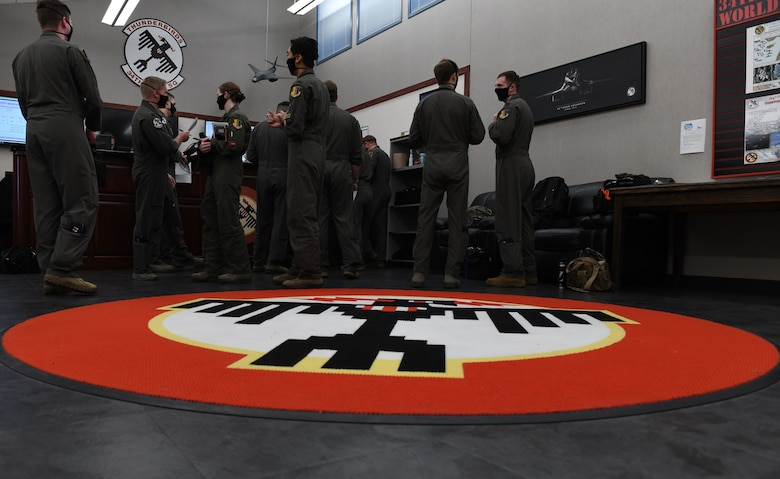 Aviators assigned to the 34th Bomb Squadron at Ellsworth Air Force Base, S.D., gather for a step briefing May 19, 2020, to receive mission plans for a long-range, long-duration Bomber Task Force mission in the U.S. European Command area of responsibility. BTF missions demonstrate the commitment of the U.S. to integrate with NATO and allied partners and ensure regional security. (U.S. Air Force photo by Airman 1st Class Christina Bennett)