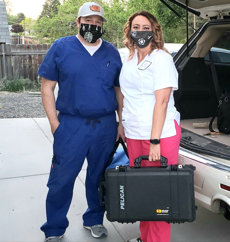 Couple pose in scrubs with face covering