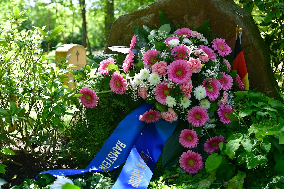 A floral wreath sits in front of a grave site.