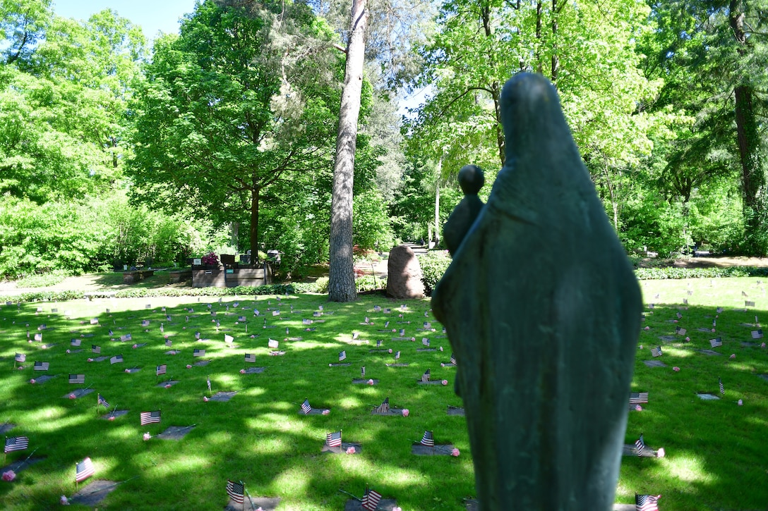 A grave site with a statue of Mary and baby Jesus in the foreground.