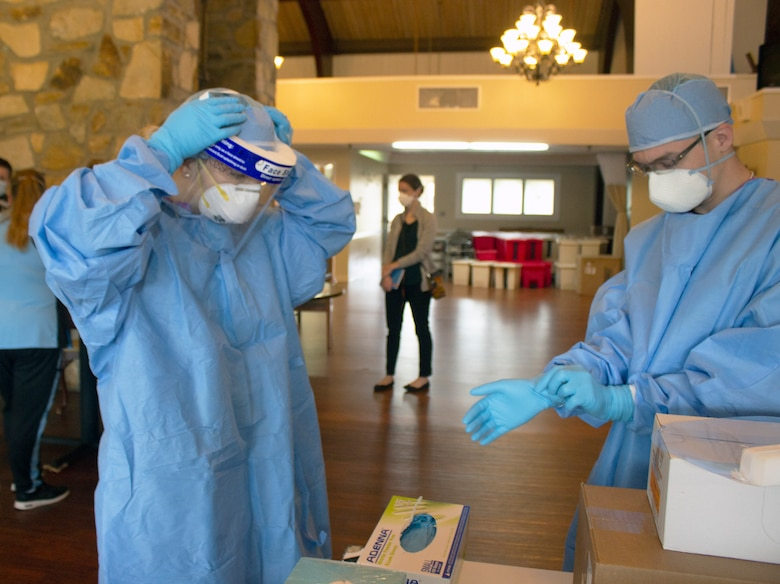 Spc Dominique Dalessio (left) and Sgt. Shane Brandes (right) adjust their face shields and personal protective equipment while preparing for the mission to administer COVID-19 tests at the Lancashire Hall Nursing and Rehab Center in Lancaster, Pa., on May 19, 2020.