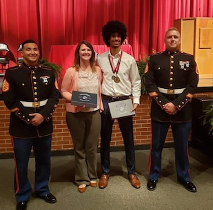 Staff Sgt. Michael Isaac and Staff Sgt. Michael Maynard, local Marine Corps recruiters, present a Battles Won Academy invitation to Robert P. Matthew, a Cairo High School student, during a visit to the high school, in Cairo, Georgia, April 24, 2019.  Matthew was one of 96 students across the country who the Marine Corps selected for the academy as part of the Semper Fidelis All-American Program. During the academy in Washington, D.C., students will participate in daily physical training with Marines, community service projects, listen to keynot speakers and more. (U.S. Marine Corps photo by Cpl. Mike Hernandez)