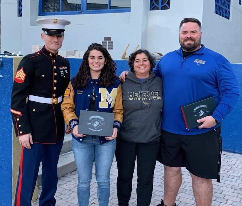 Sgt. Jesse Hoffman, a recruiter with Recruiting Station Jacksonville, presents a Battles Won Academy invitation to Lauren Prosuch, a Pedro Menendez High School student, at her high school in Palm Coast, Florida, March 6, 2019. Prosuch was one of 96 Semper Fidelis All-Americans chosen from across the nation to attend the Battles Won Academy in Washington D.C. The academy features daily physical training with Marines, community service projects, leadership training, keynote speakers and more. (U.S. Marine Corps photo by Cpl. Mike Hernandez)