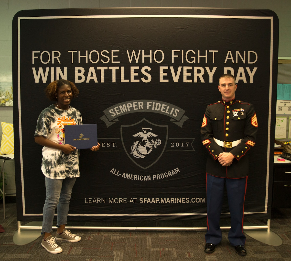Haley Bishop, left, receives a congratulatory certificate for attending the 2019 Semper Fidelis All-American Program Battles Won Academy, July 11-15, in Washington, D.C.