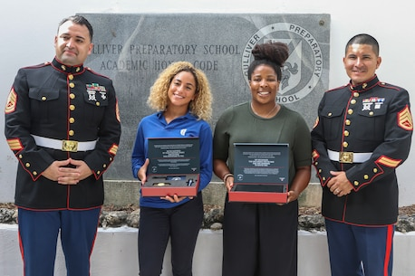 Mekayla Frazier (second from left), a junior at Gulliver Preparatory Academy, Pinecrest, Florida, formally accepts an invitation to participate in the Marine Corps' Semper Fidelis All-American Program from Gunnery Sgt. Isaac Cordeiro (left), the staff noncommissioned officer-in-charge of Recruiting Substation South Dade, and Staff Sgt. Victor Buendia (right), the assistant SNCOIC of RSS South Dade, at her high school, May 10, 2019. By accepting the Marine Corps' invitation, Frazier, a 17-year-old native of Pinecrest, will get the opportunity to attend the Battles Won Academy, a four-day leadership and development workshop in Washington, D.C., along with 95 other students from across the nation. During the academy, they will participate in daily physical training with Marines, receive leadership instruction, participate in community service projects, listen to keynote speakers and engage in a variety of other activities that familiarize them with Marine Corps values and leadership principles.