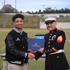 Kris Evans, a high school senior from Union Christian Academy and 2019 Semper Fidelis All-American, receives a Semper Fidelis All-American Program certificate of achievement from U.S. Marine Corps Sgt. Rodion Zabolotniy, a recruiter with Marine Corps Primary Contact Station Ruston, at the UCA Sports Complex in Farmerville, Louisiana, Oct. 11, 2019.