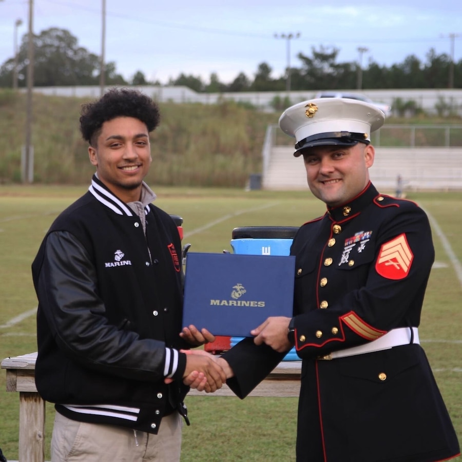 Kris Evans, a high school senior from Union Christian Academy and 2019 Semper Fidelis All-American, receives a Semper Fidelis All-American Program certificate of achievement from U.S. Marine Corps Sgt. Rodion Zabolotniy, a recruiter with Marine Corps Primary Contact Station Ruston, at the UCA Sports Complex in Farmerville, Louisiana, Oct. 11, 2019. Evans was selected not only for his athletic performance but for outstanding character, academic excellence, and community leadership that reflects the Marine Corps' values of honor, courage, and commitment. Less than 100 students from across the nation attended the academy this past summer in Washington, D.C. (U.S. Marine Corps photo by Sgt. Shellie Hall)