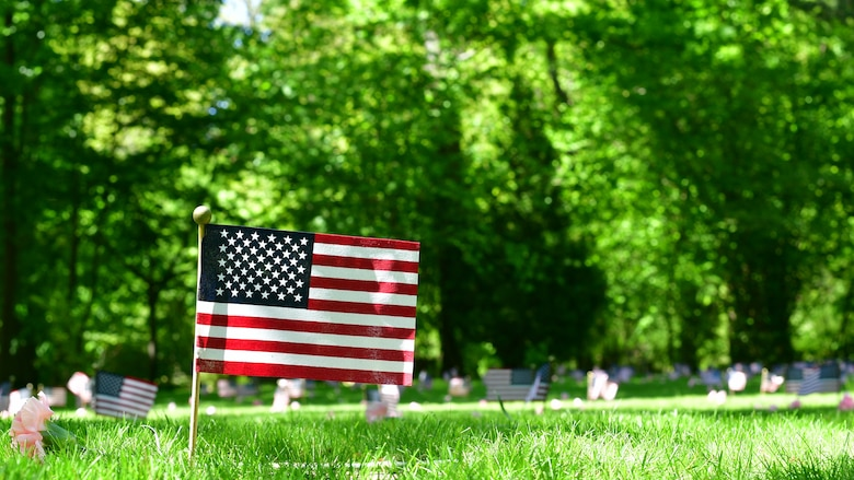 An American flag stands next to a grave at a memorial site in a cemetery.