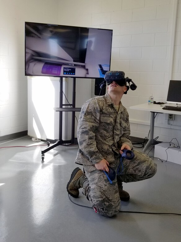 Airman 1st Class Cole Musgrove 461st Aircraft Maintenance Squadron aircraft maintainer, looks inside a virtual landing gear compartment of the E-8C Joint Surveillance Target Attack Radar System aircraft at Robins Air Force Base, Georgia, April 13, 2020. Virtual reality was brought to Team JSTARS to assist training maintainers remotely in a controlled environment.