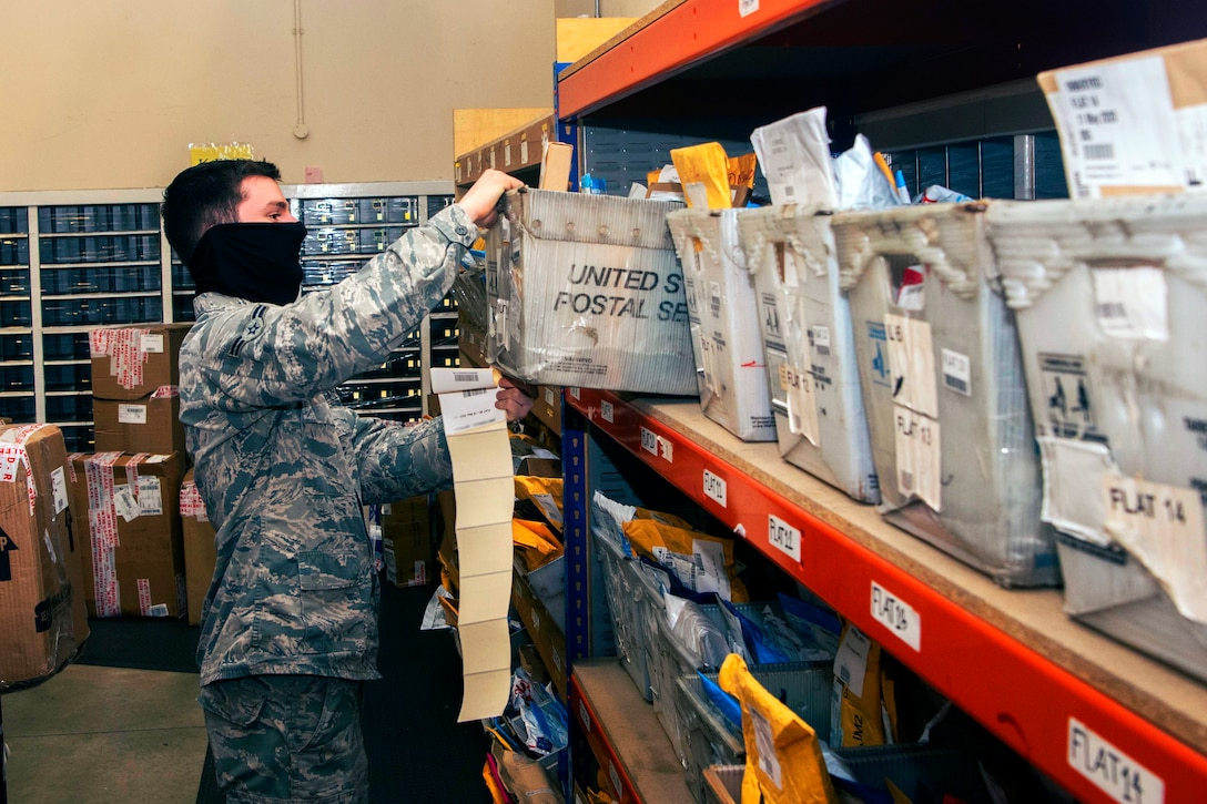 An airman in a mask puts a box of mail on the shelf inside a post office.