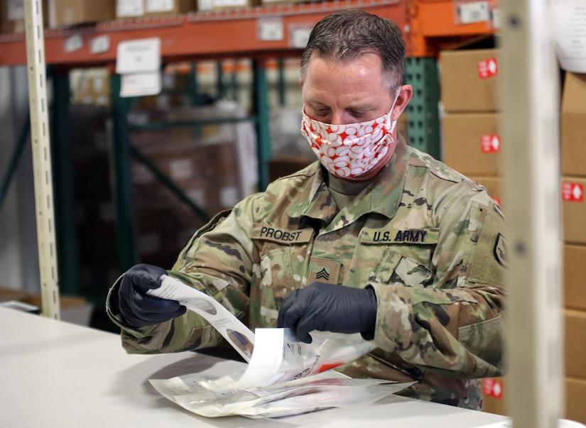A guardsman assembles a COVID-19 test kit.
