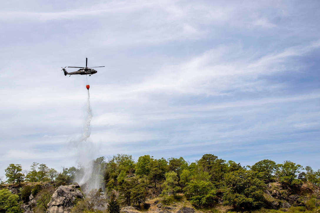 An Army helicopter drops water from a bucket over a tree line.