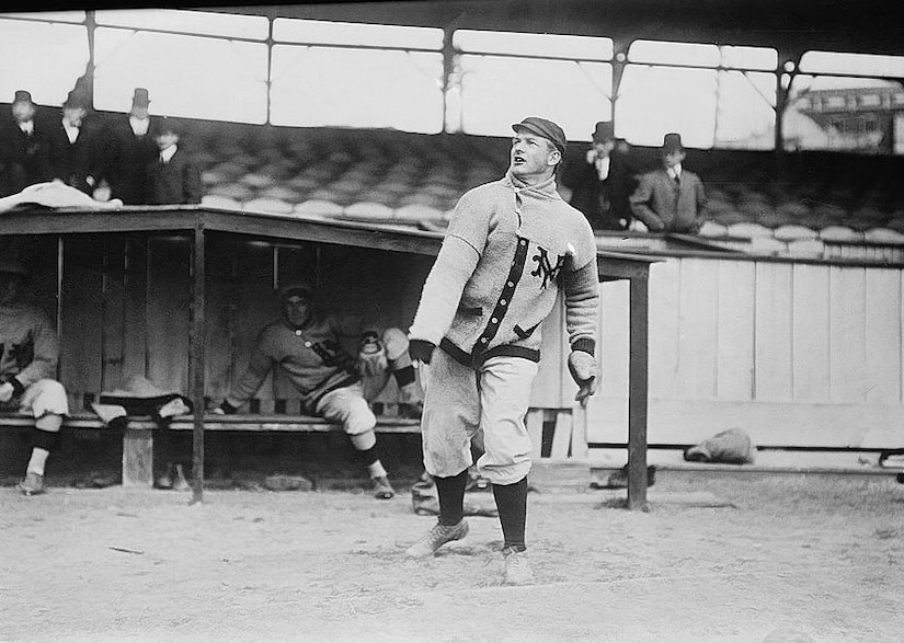 A baseball pitcher wearing a New York Giants sweater warms up in front of a dugout.
