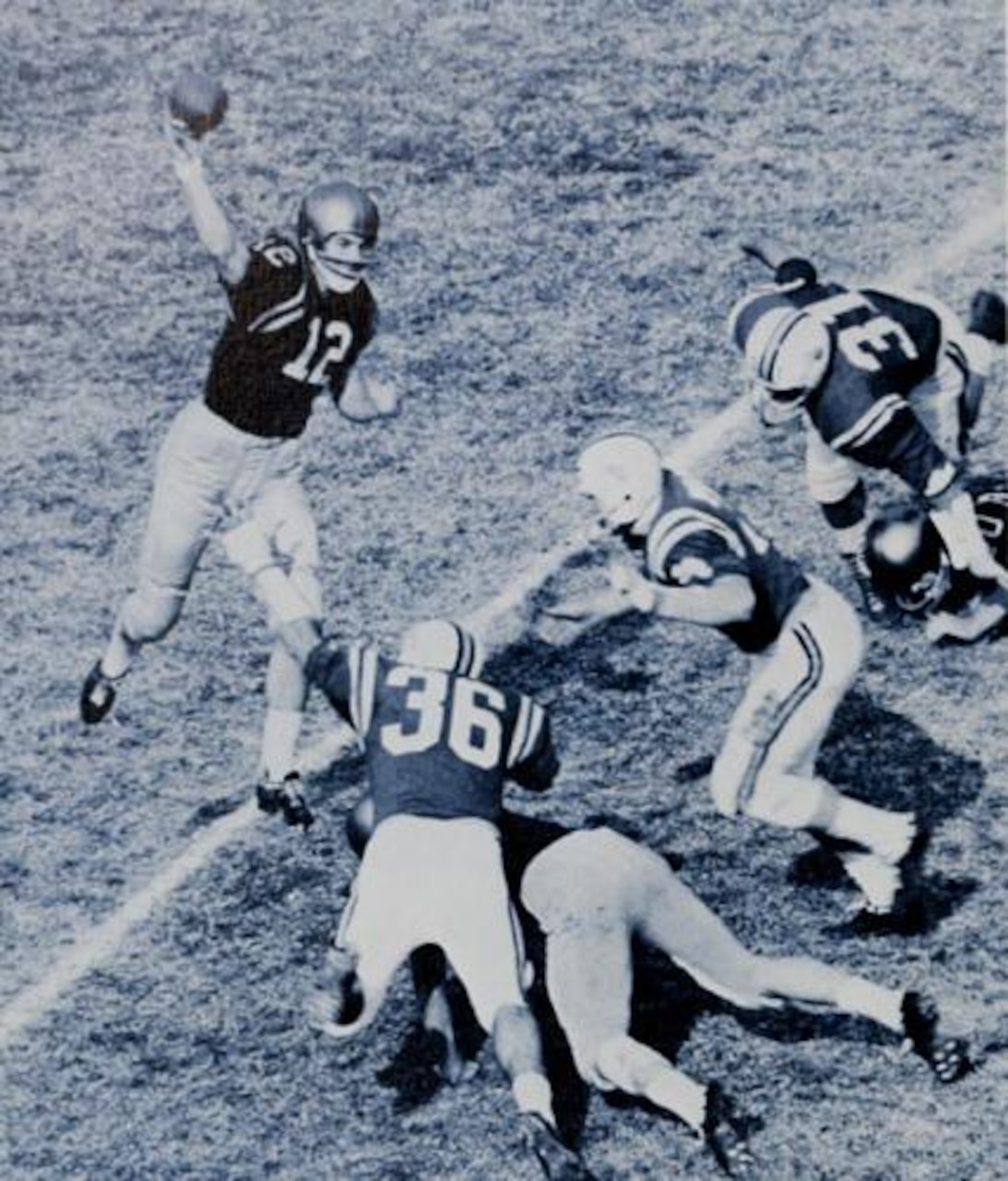 A quarterback prepares to throw the ball as the defensive line approaches.