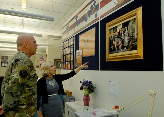 "Flag room Supervisor Linda Farrell points to an embroidered flag depicting President George Washington and Betsy Ross with U.S. Space Force Commander Gen. John W. ""Jay"" Raymond"