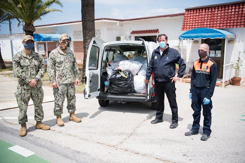 Sailors stand next to a van full of bags of donated goods.