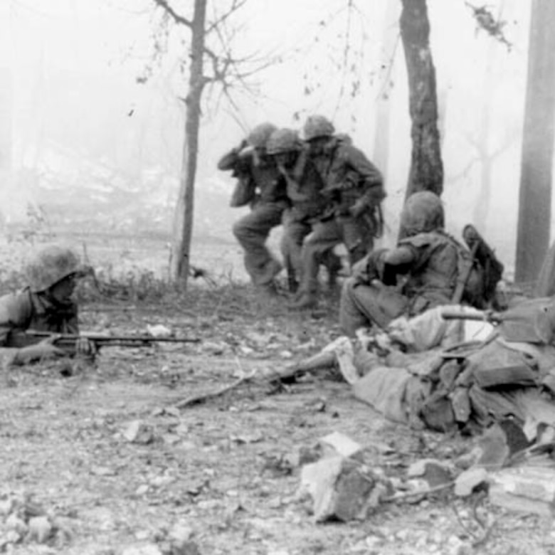 Two soldiers carry an injured soldier while three soldiers lay down on the ground to provide cover fire.