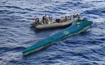 A Coast Guard boarding team in a boat approach a low profile semi-submersible.