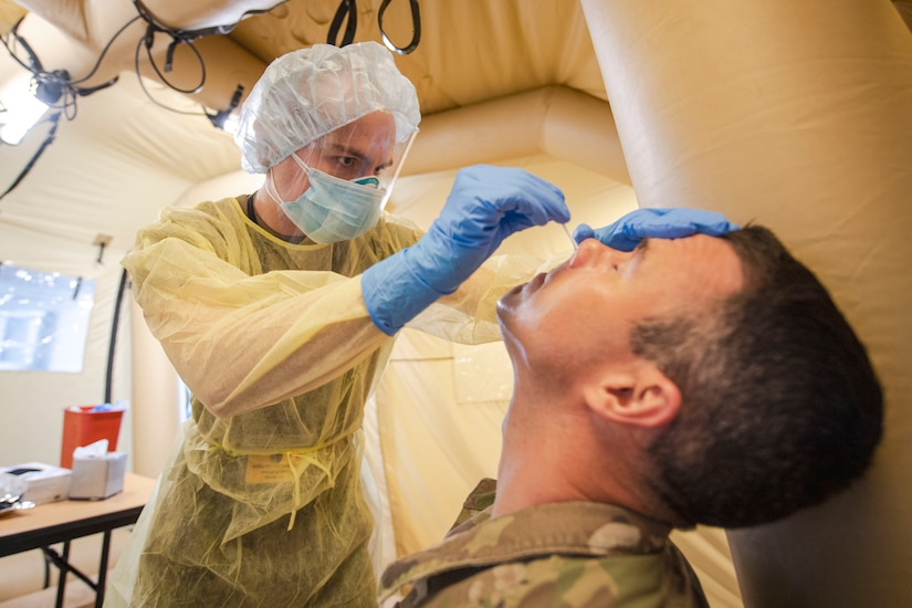 A health care provider clad in protective gear conducts a nasal swab test on a service member.