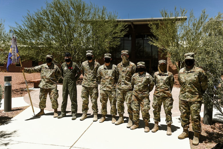 Airmen from the 99th Contracting Squadron dressed in OCPs and wearing facemasks stand alongside Col. James Price, 432nd Wing/432nd Air Expeditionary Wing vice commander and Chief Master Sgt. Michelle Browning, 432nd WG/AEW command chief, as they pose for a group photo.