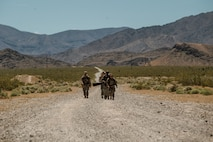 Airmen from the 99th Contracting Squadron dress in their OCPs march down a dirt path in the summer Nevada sun with mountains in the background.