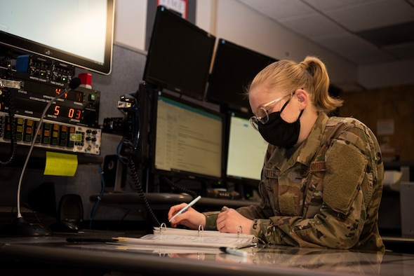 Airman Basic Julia Hitter, 30th Space Wing Command Post junior emergency actions controller, goes through a shift changeover checklist May 18, 2020, at Vandenberg Air Force Base, Calif. During the COVID-19 pandemic, the 30th SW Command Post has taken on the responsibility of creating daily situation reports for the U.S. Air Force and Space Force that detail the status of Vandenberg AFB and the response the base is taking towards COVID-19, on top of their every-day workload. (U.S. Air Force photo by Senior Airman Hanah Abercrombie)