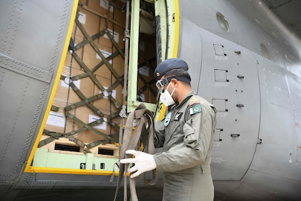 A Pakistani aircrew member gathers straps off a Pakistan air force C-130 at Joint Base Andrews, Md., May 21, 2020. During the event, Ambassador Asad Majeed Khan, an official from the Pakistani Embassy, highlighted the historic ties between the people of the U.S. and Pakistan and their armed forces. Khan also noted the armed forces of both countries have fought together in the Global War on Terrorism and stand together in the fight against the COVID-19 pandemic. (U.S. Air Force photo by Airman 1st Class Spencer Slocum)