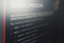 White text is on a screen detailing the syllabus and course curriculum of the Archer University program.