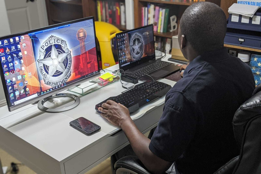 A man at a desk observes two computer screens while using a computer.