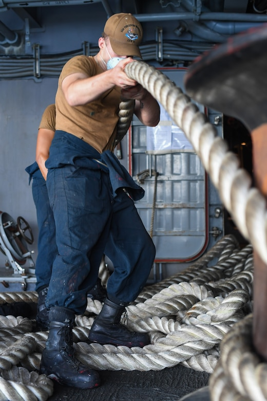 Two sailors handle rope aboard a naval vessel.
