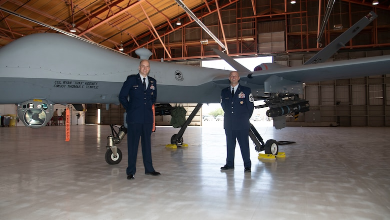 Col. Ryan Keeney, 49th Wing commander and Chief Master Sgt. Thomas Temple, 49th WG command chief, pose in front of an MQ-9 Reaper, May 21, 2020, on Holloman Air Force Base, N.M. Keeney assumed command of the 49th WG during a formal ceremony. (U.S. Air Force photo by Tech. Sgt. BreeAnn Sachs)