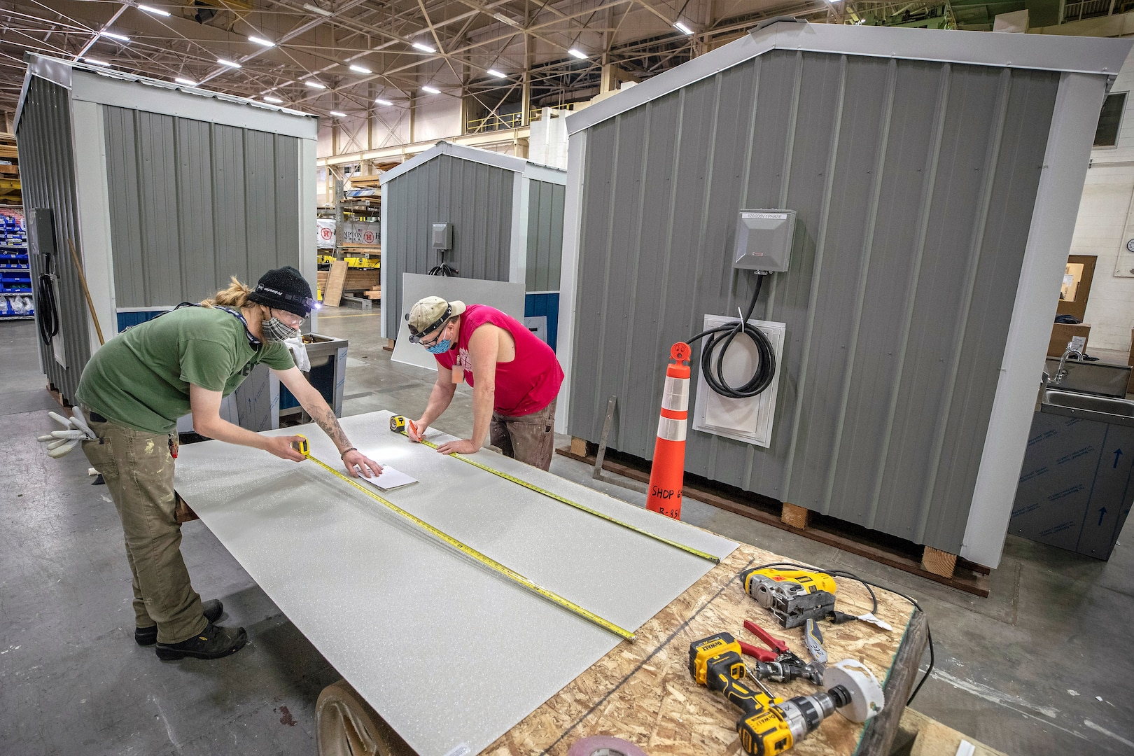 Peyton Gingrey, left, and James Zeitler, both composite plastic fabricators with Shop 64, assemble new hand washing stations May 19, 2020 inside Shop 64 Woodcrafters at Puget Sound Naval Shipyard & Intermediate Maintenance Facility in Bremerton, Washington.