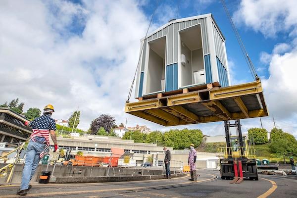 Shop 740 crew members lift a new hand washing station into Dry Dock 4 May 19, 2020 at Puget Sound Naval Shipyard & Intermediate Maintenance Facility in Bremerton, Washington.