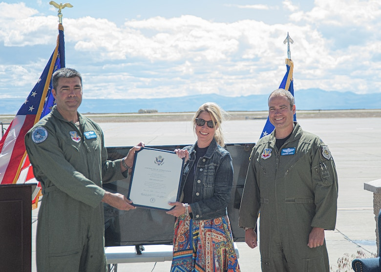 "U.S. Air Force Col. Richard A. Goodman, 366th Fighter Wing commander, (left) gives Gina Lapp, wife of Lt. Col. Aaron C. ""Badger"" Lapp, (mid) a certificate of appreciation, May 15, 2020, on Mountain Home Air Force Base, Idaho. Lapp has been involved in significant deployments such as Operation INHERENT RESOLVE and Operation DELIBERATE RESOLVE. (U.S. Air Force photo by Airman 1st Class Akeem K. Campbell)"