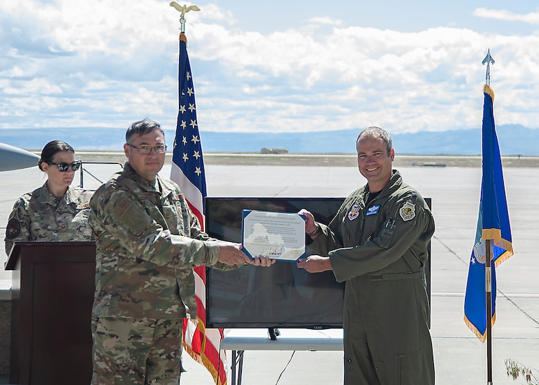 "U.S. Air Force Senior Master Sgt. David Schummer, 366th Fighter Wing superintendent of operations and plans, presents Lt. Col. Aaron C. ""Badger"" Lapp, 366th Fighter Wing director of operations and plans, the certificate of appreciation, May 15, 2020, on Mountain Home Air Force Base, Idaho. Lapp has been involved in significant deployments such as Operation INHERENT RESOLVE and Operation DELIBERATE RESOLVE. (U.S. Air Force photo by Airman 1st Class Akeem K. Campbell)"