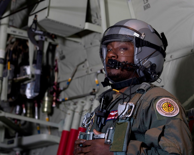 Staff Sgt. Marcus Wright, 36th Airlift Squadron C-130J Super Hercules loadmaster, briefly looks at the camera before opening the door to get formation flight documentation during Yokota Air Base, Japan's Samurai Surge training exercise, May 21, 2020.