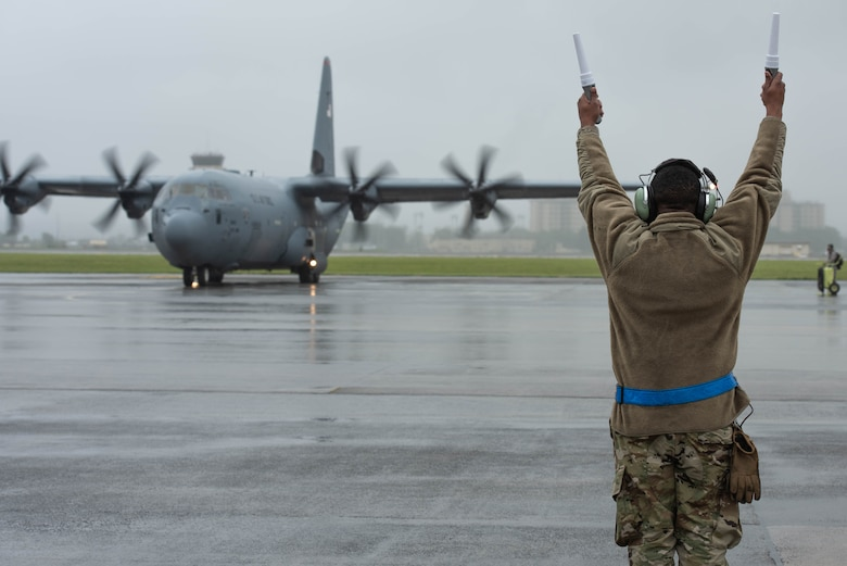 A crew chief, assigned to the 374th Aircraft Maintenance Squadron, marshals a C-130J Super Hercules during the 374th Airlift Wing's Samurai Surge training exercise, May 21, 2020, at Yokota Air Base, Japan.