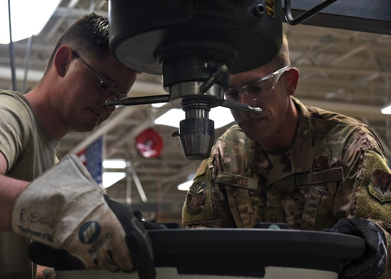 A photo of two Airmen working working with tools.