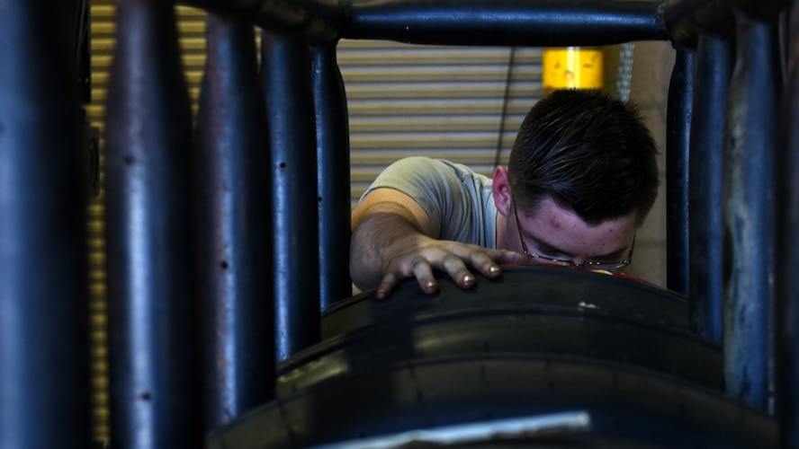 A photo of an Airman inspecting a tire