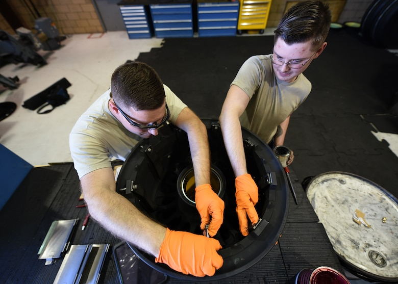 A photo of two Airmen working on a tire.