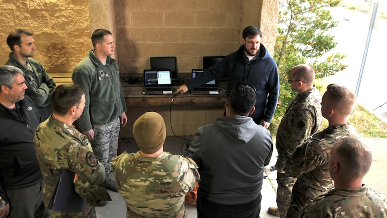 Airmen standing in front of laptops outside.