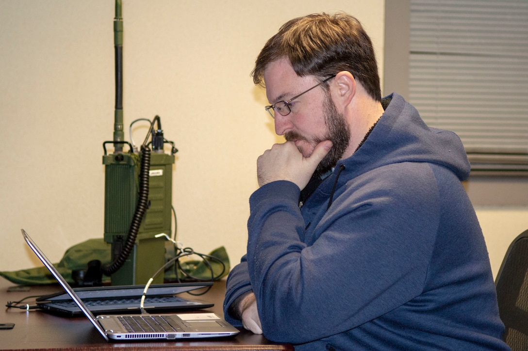 Man sitting in front of laptop with tactical radio on table.