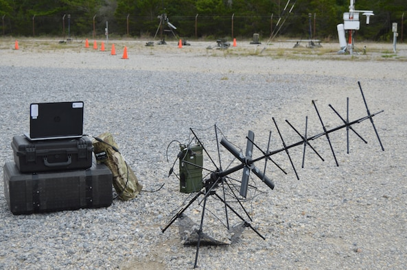 A laptop, tactical radio, satellite antenna and carrying cases sitting outside.