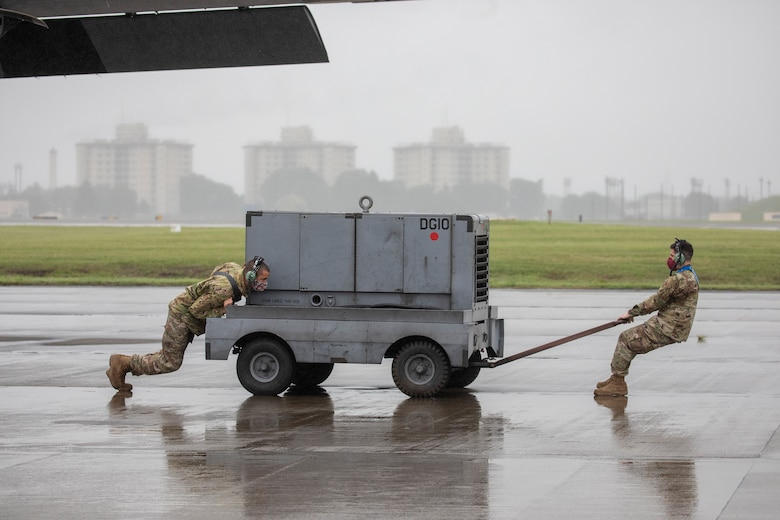 Crew chiefs assigned to the 374th Aircraft Maintenance Squadron push an A/M32 diesel generator into position prior to starting a C-130J Super Hercules during the Samurai Surge training exercise at Yokota Air Base, Japan, May 21, 2020.