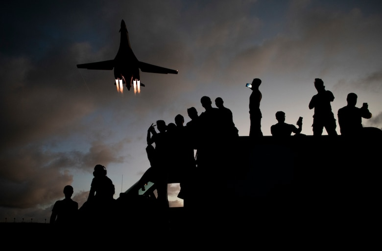 9th Expeditionary Bomb Squadron B-1B Lancer mechanics take selfies as a B-1B flies overhead at Andersen Air Force Base, Guam, May 21, 2020. In continued demonstration of the U.S. Air Force's dynamic force employment model, two U.S. Air Force B-1B Lancers flew from Andersen AFB and conducted training in Alaska and near Misawa Air Base, Japan.  The 9th EBS deployed to Guam from Dyess Air Force Base, Texas, along with 200 Airmen assigned to the 7th Bomb Wing at Dyess AFB, Texas, as part of a Bomber Task Force and is supporting Pacific Air Forces' strategic deterrence missions and commitment to the security and stability of the Indo-Pacific region. (U.S. Air Force photo by Senior Airman River Bruce)