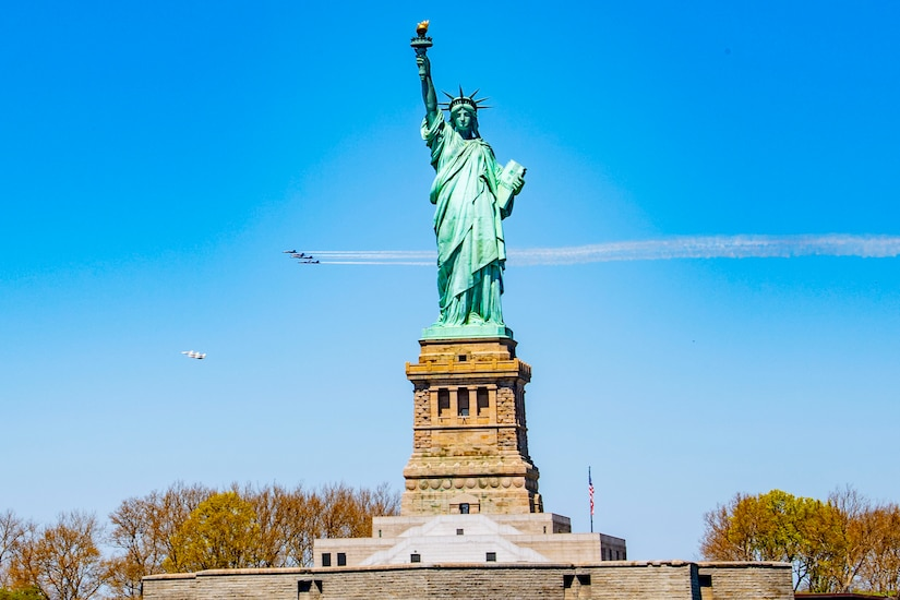 A group of military jets fly over the Statue of Liberty.