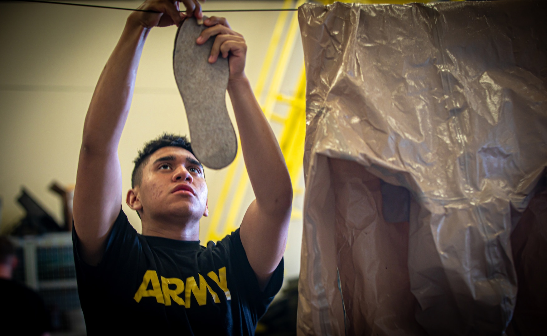 An Alabama National Guard Soldier with a Task Force 31 disinfection team hangs up his personal protective suit to dry in a Fort Whiting hangar in Mobile, Alabama, May 15, 2020.