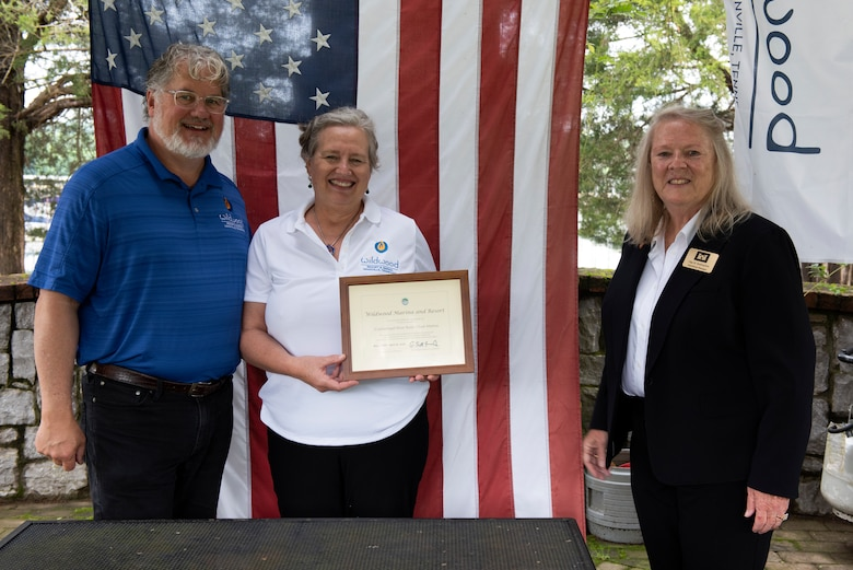 """Olga Beddingfield (Right), U.S. Army Corps of Engineers Nashville District's Mid-Cumberland Area Operations manager, presents a certificate of achievement to John and Natasha Deane, owners of Wildwood Resort and Marina, during a """"Clean Marina"""" dedication May 21, 2020 at the resort located at Cordell Hull Lake in Granville, Tennessee.  The event recognized the marina's voluntary efforts to reduce water pollution and erosion in the Cumberland River watershed, and for promoting environmentally responsible marina and boating practices. (USACE photo by Lee Roberts)"""